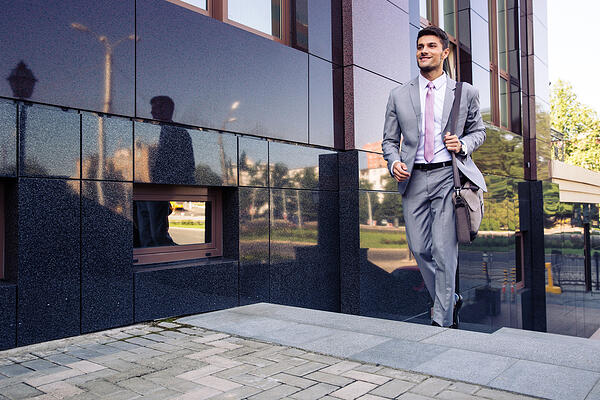 Happy businessman walking on stairs outdoors